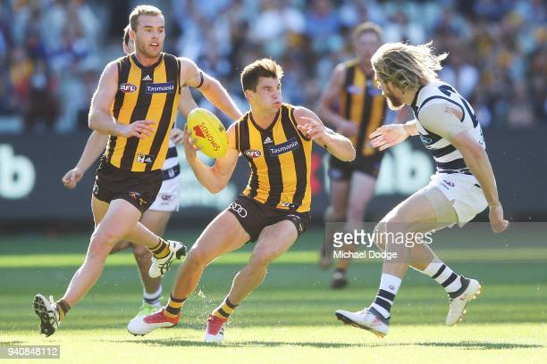 Jaeger O'Meara of the Hawks looks upfield next to teammate Tom Mitchell of the Hawks and past Cameron Guthrie of the Cats during the round two AFL...