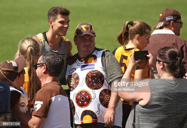 Jaeger O'Meara of the Hawks signs autographs and poses for photo with supporters in the crowd during a Hawthorn Hawks AFL training session at...