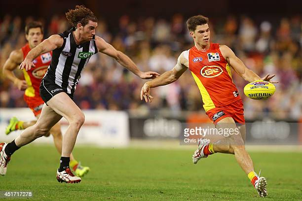 Jaeger O'Meara of the Suns kicks away from Tyson Goldsack of the Magpies during the round 16 AFL match between the Gold Coast Suns and the...