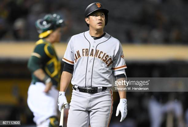 JaeGyun Hwang of the San Francisco Giants looks on as he walks back to the dugout after striking out looking against the Oakland Athletics in the top...