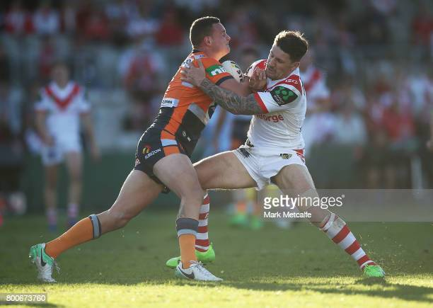 Jaelen Feeney of the Knights is tackled by Gareth Widdop of the Dragons during the round 16 NRL match between the St George Illawarra Dragons and the...