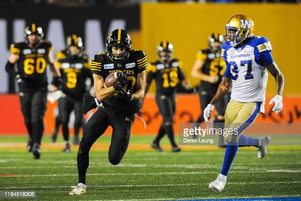 Jaelon Acklin of the Hamilton Tiger-Cats runs the ball against Brandon Alexander of the Winnipeg Blue Bombers during the 107th Grey Cup Championship...