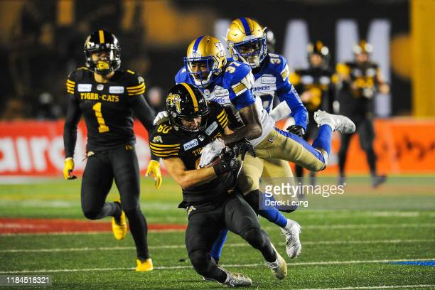 Jaelon Acklin of the Hamilton Tiger-Cats runs the ball against Brandon Alexander of the Winnipeg Blue Bombers during the 107th Grey Cup Championship...