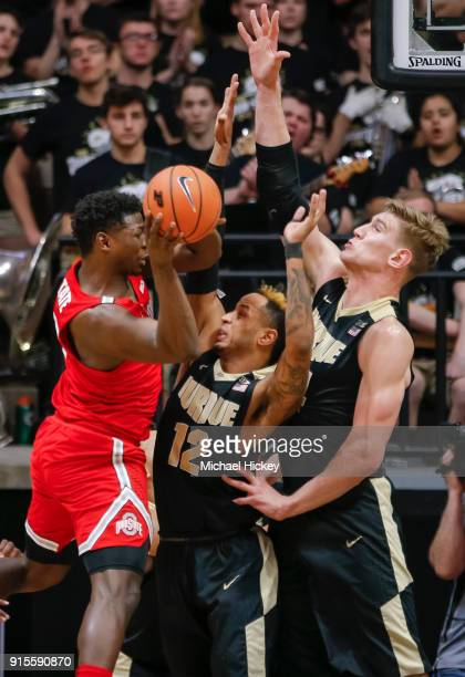 Jae'Sean Tate of the Ohio State Buckeyes looks to pass the ball off as Vincent Edwards and Isaac Haas of the Purdue Boilermakers defend at Mackey...