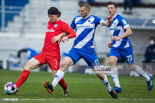 Jae-sung Lee of Kiel is challenged by Lars Lukas Mai of Darmstadt during the Second Bundesliga match between SV Darmstadt 98 and Holstein Kiel at...