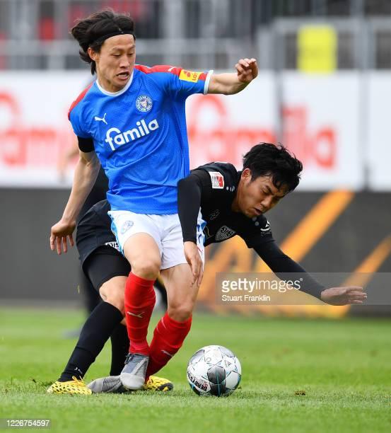 Jae-sung Lee of Kiel is challenged by Wataru Endo of Stuttgart during the Second Bundesliga match between Holstein Kiel and VfB Stuttgart at...
