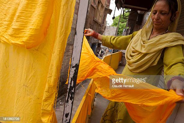 Jaffa Reilly's wife putting cloth to dry on a balcony in street of Jodhpur