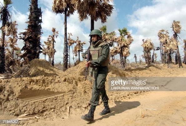 A Sri Lankan soldier patrols along the A-9 highway along a 'de facto
