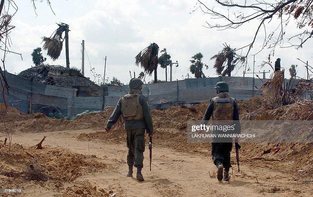 Sri Lankan soldiers patrol along the main A-9 highway along a 'de