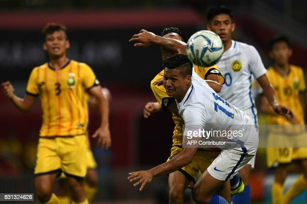 Jafri Firdaus Chew of Malaysia heads the ball against Brunei players during their men's football Group A match at the 29th Southeast Asian Games at...