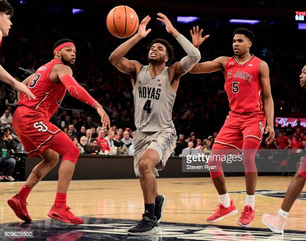 Jagan Mosely of the Georgetown Hoyas is defended by Marvin Clark II and Justin Simon of the St John's Red Storm during the first round of the Big...