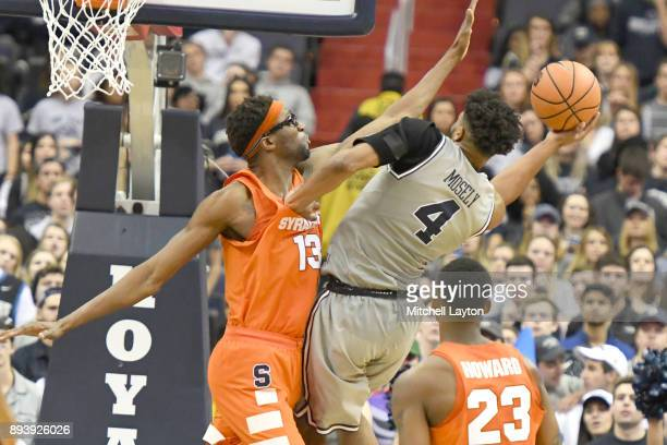 Jagan Mosely of the Georgetown Hoyas tries to take a shot over Paschal Chukwu of the Syracuse Orange during a college basketball game at Capitol One...