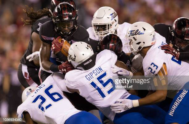 Jager Gardner of the Temple Owls runs the ball and is tackled by Akayleb Evans, Trevis Gipson, and Zaven Collins of the Tulsa Golden Hurricane in the...
