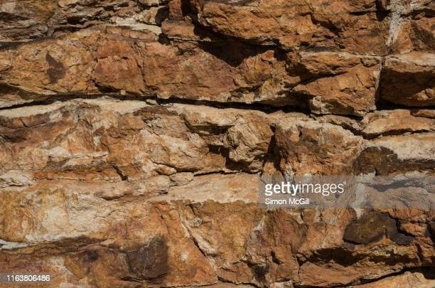 jagged orange sandstone rock face on the top of mount ainslie in canberra, australian capital territory, australia - extreme terrain stock pictures, royalty-free photos & images