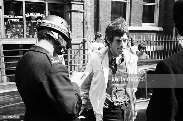 Jagger's Girlfriend Chrissie Shrimpton looks on as Mick has his particulars taken by a patrolman