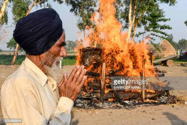 Jagir Singhstands next to the burning pyre of his son, soldier Satnam Singh who was killed in a recent clash with Chinese forces in the Galwan...