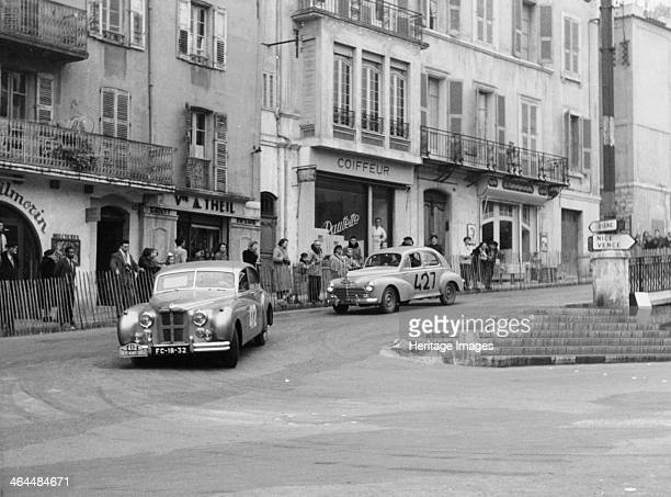Jaguar and Peugeot Monte Carlo Rally 1954 A 1953/4 3442cc Jaguar Mk VII leading a 1953/4 1290cc Peugeot 203 on a bend with spectators behind a barrier