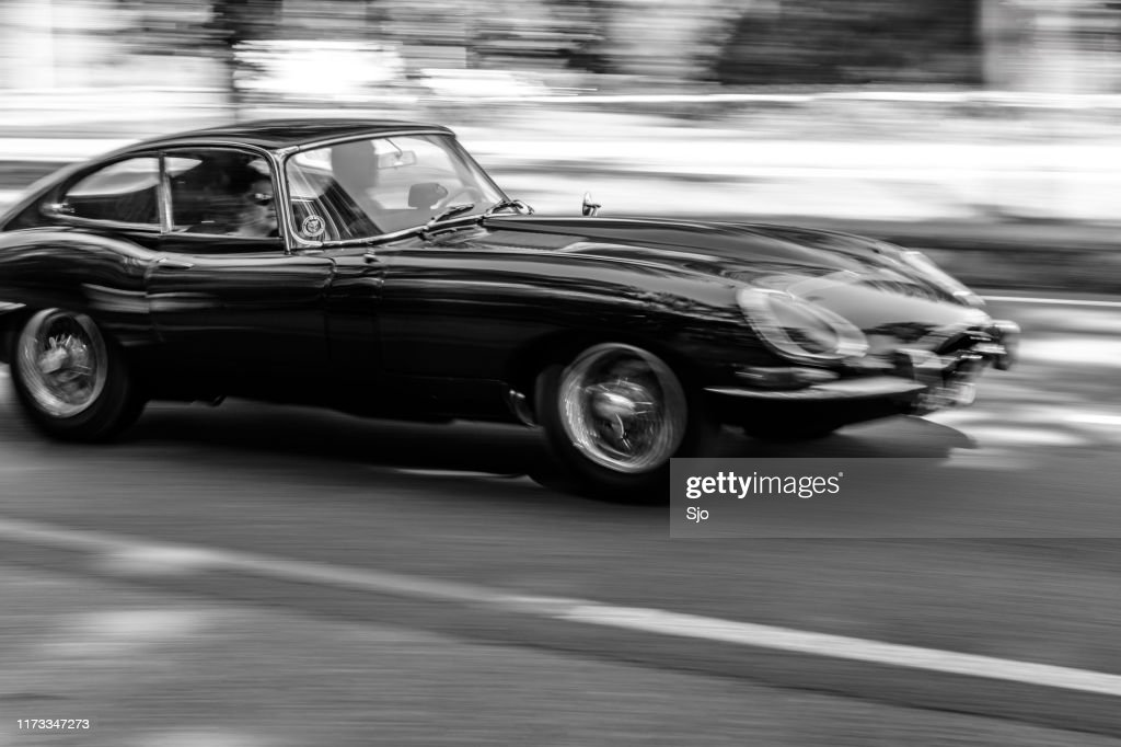 Jaguar E-Type driving at high speed on a road through a forest : Stock Photo