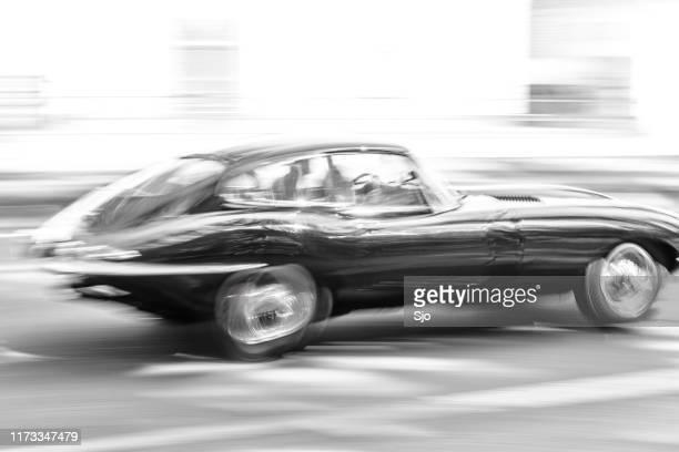 jaguar e-type guida ad alta velocità su una strada attraverso una foresta - jaguar foto e immagini stock