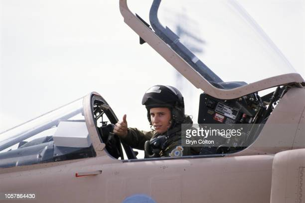 Jaguar fighter pilot gives the 'thumbs up' gesture as he prepares to leave his base at RAF Coltishall in his specially camouflaged aircraft for...
