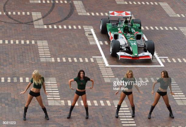 Jaguar pit girls perform a dance routine in front of the new Jaguar R5 F1 car at Circular Quay March 2 2004 in Sydney Australia