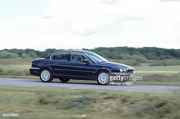Jaguar X type driving along road 2000