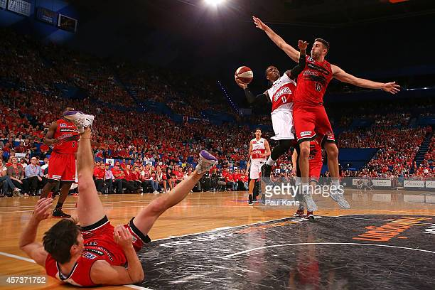 Jahil Carson of the Hawks drives to the basket against Damian Martin and Tom Jervis of the Wildcats during the round two NBL match between the Perth...