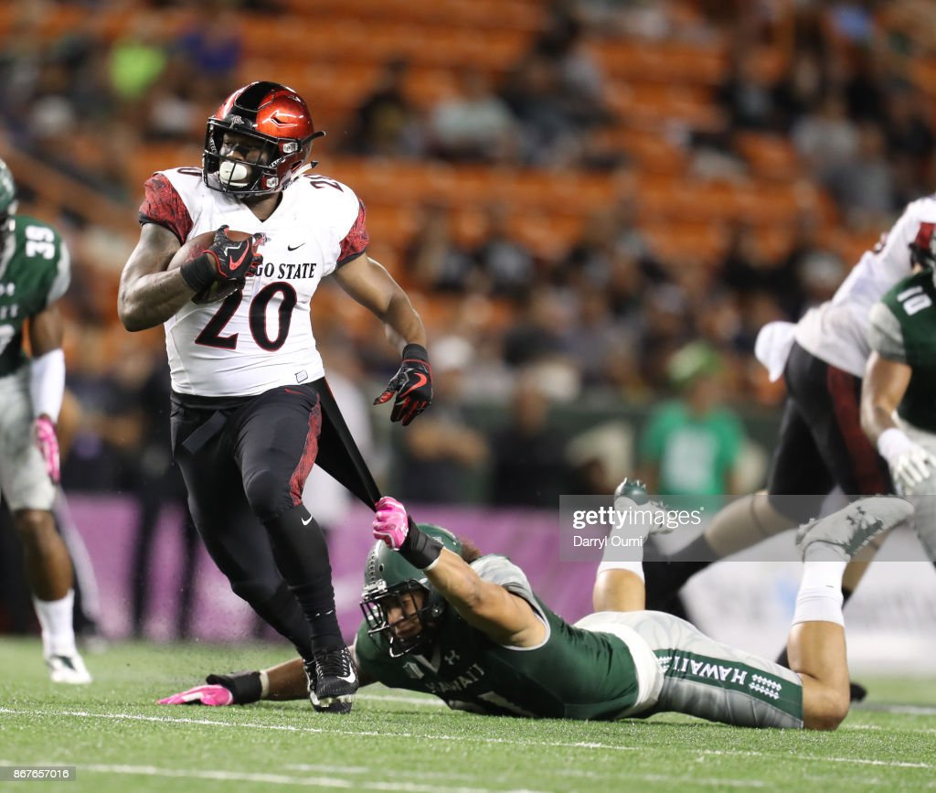 official photos 32952 e16fd Jahlani Tavai of the Hawaii Rainbow Warriors holds on to the ...