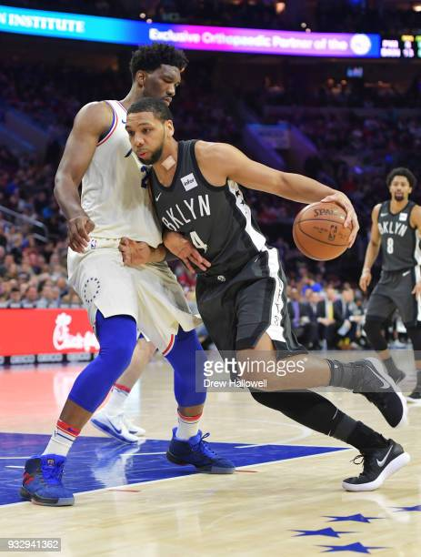 Jahlil Okafor of the Brooklyn Nets tries to drives past Joel Embiid of the Philadelphia 76ers at the Wells Fargo Center on March 16 2018 in...