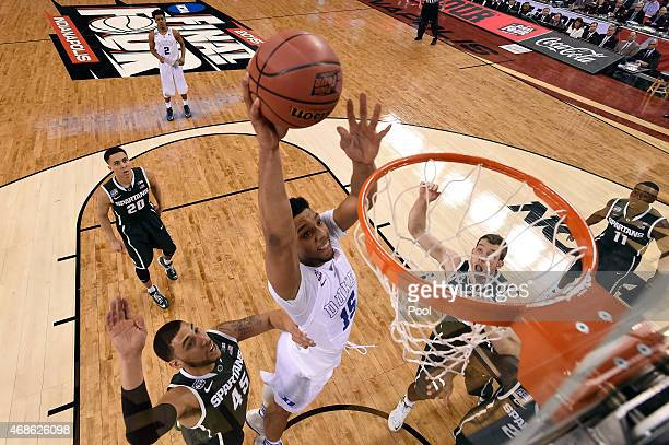 Jahlil Okafor of the Duke Blue Devils goes up for a dunk in the first half against Denzel Valentine of the Michigan State Spartans during the NCAA...