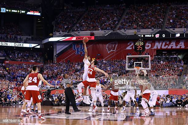 Jahlil Okafor of the Duke Blue Devils tips off against Frank Kaminsky of the Wisconsin Badgers to start the first half of the NCAA Men's Final Four...