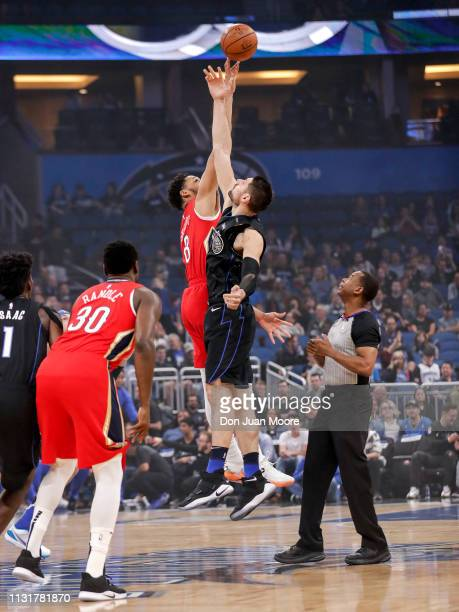 Jahlil Okafor of the New Orlean Pelicans goes up on the opening tip ball with Nikola Vucevic of the Orlando Magic during the game at the Amway Center...