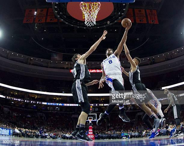 Jahlil Okafor of the Philadelphia 76ers attempts a shot over Boban Marjanovic of the San Antonio Spurs on December 7 2015 at the Wells Fargo Center...