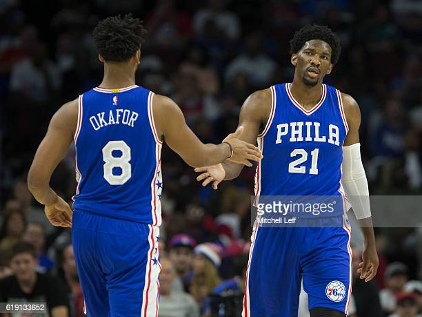 Jahlil Okafor of the Philadelphia 76ers slaps hands with Joel Embiid against the Oklahoma City Thunder at Wells Fargo Center on October 26 2016 in...