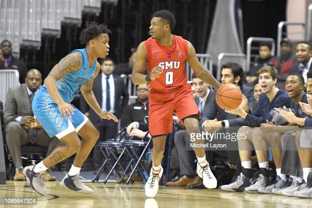 Jahmal McMurray of the Southern Methodist Mustangs dribbles around James Akinjo of the Georgetown Hoyas during a college basketball game at the...