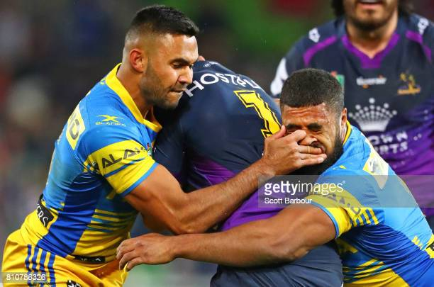 Jahrome Hughes of the Storm is tackled by Michael Jennings of the Eels during the round 18 NRL match between the Melbourne Storm and the Parramatta...