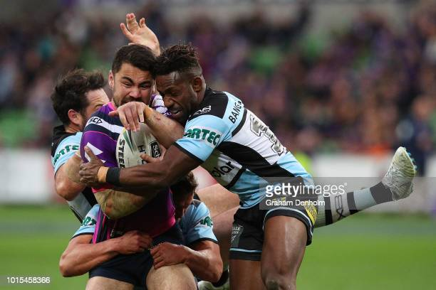 Jahrome Hughes of the Storm is tackled during the round 22 NRL match between the Melbourne Storm and the Cronulla Sharks at AAMI Park on August 12...