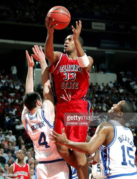 Jahsha Bluntt of the Delaware State Hornets goes in for a layup over JJ Redick and Sean Dockery of the Duke Blue Devils during their first round NCAA...