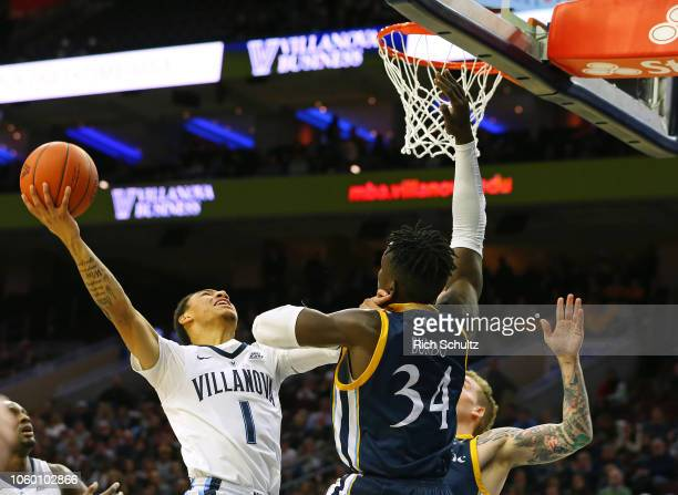 Jahvon Quinerly of the Villanova Wildcats attempts a shot as Abdulai Bundu and Travis Atson of the Quinnipiac Bobcats defend during the first half of...