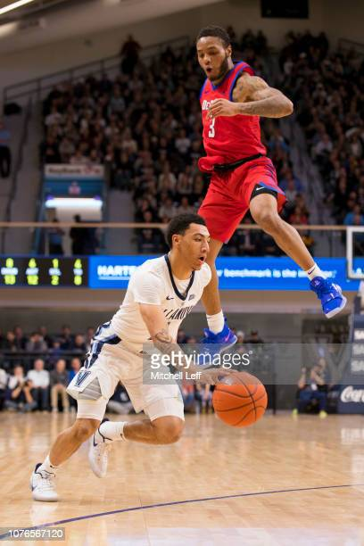 Jahvon Quinerly of the Villanova Wildcats drives to the basket against Devin Gage of the DePaul Blue Demons in the first half at Finneran Pavilion on...