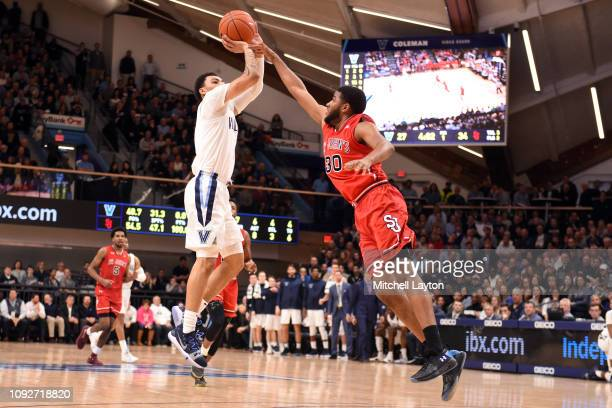 Jahvon Quinerly of the Villanova Wildcats takes a jump shot over LJ Figueroa of the St John's Red Storm during a college basketball game at the...