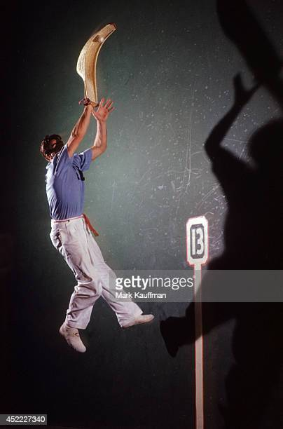 Portrait of player in action using lateral wall to reach pelota with cesta during photo shoot at Biscayne Fronton Miami FL CREDIT Mark Kauffman