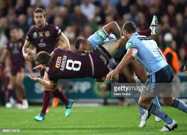 Jai Arrow of Queensland is tackled by Paul Vaughan of the Blues during game three of the State of Origin series between the Queensland Maroons and...