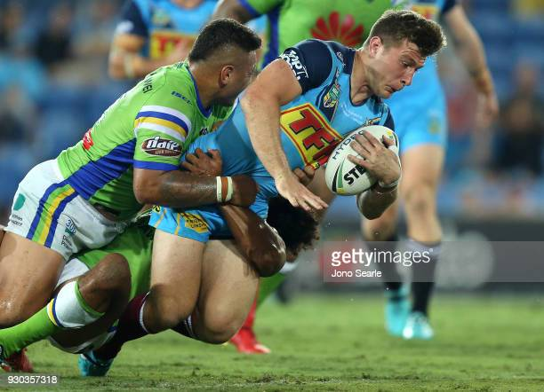 Jai Arrow of the Titans is tackled during the round one NRL match between the Gold Coast Titans and the Canberra Raiders at Cbus Super Stadium on...