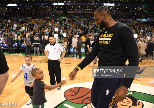 Jaiden son of Isaiah Thomas of the Boston Celtics high fives with LeBron James of the Cleveland Cavaliers on April 5 2017 at the TD Garden in Boston...