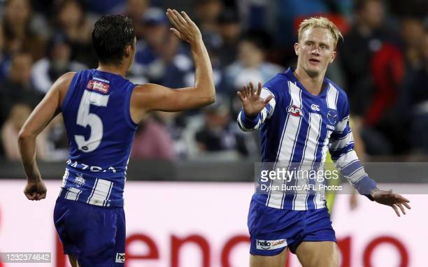 Jaidyn Stephenson of the Kangaroos celebrates a goal with Curtis Taylor during the 2021 AFL Round 05 match between the Geelong Cats and the North...