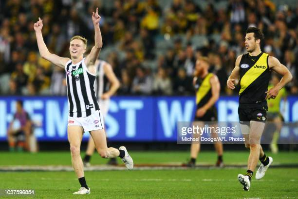 Jaidyn Stephenson of the Magpies celebrates the win on the final siren next to Alex Rance of the Tigers during the AFL Preliminary Final match...