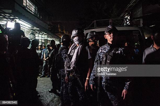 Jail guards armed with assault weapons guard outside a city jail where 10 prisoners with various drug charges were killed in an alleged grenade blast...