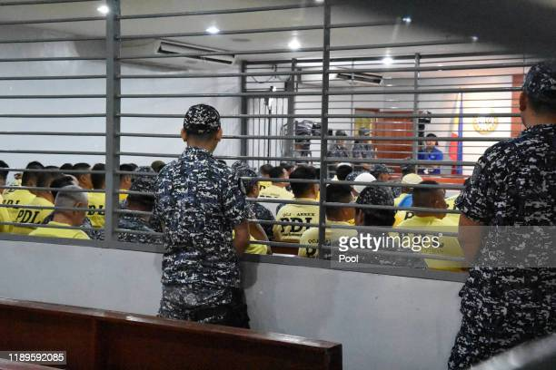 Jail guards stand next to a crowd of accused in the Maguindanao massacre wait for the promulgation at the trial venue inside a prison facility on...