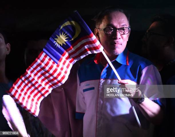 Jailed former opposition leader and current federal opposition leader Anwar Ibrahim waves the Malaysian flag to the supporters during a rally in...